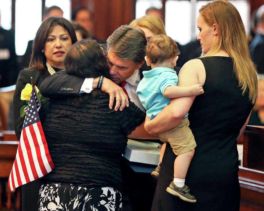 Gov. Rick Perry hugs Rufina Aranda, the mother of Sgt. Lorenzo Aranda Jr., along with his wife, Heather Scott, and their son, Lorenzo Aranda, after presenting his family with a flag while honoring fallen Texas military members during a special joint session of the Senate and House of Representatives on Saturday. Photo: Tom Reel, San Antonio Express-News
