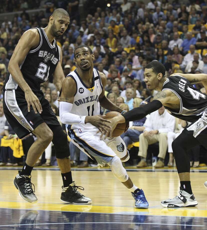 The Grizzlies' Mike Conley (11) drives between Spurs' Tim Duncan (21) and Danny Green (4) in the first half of Game 3 of the 2013 Western Conference Finals at the FedEx Forum in Memphis on Saturday, May 25, 2013. (Kin Man Hui / San Antonio Express-News)