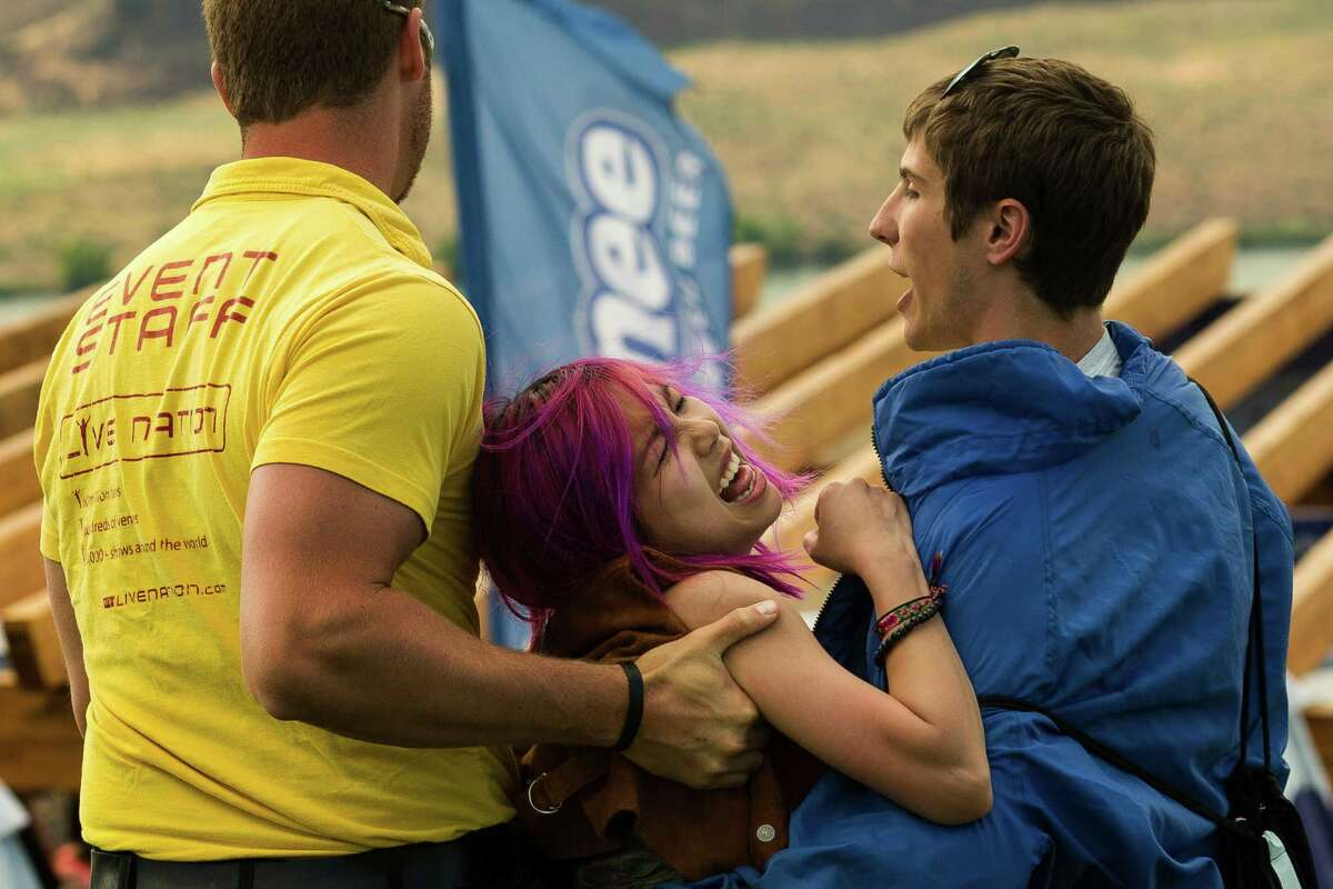 An unwilling attendee is removed from the main stage area by event staff on the second day of the annual Sasquatch music festival Saturday, May 25, 2013, at The Gorge Amphitheatre in George.