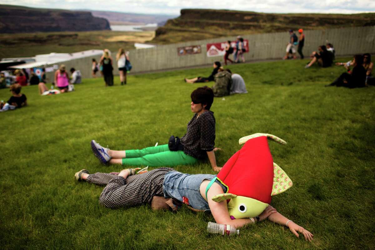 In the hills overlooking the Columbia River, a woman encased in a fish costume takes a rest on the second day of the annual Sasquatch music festival Saturday, May 25, 2013, at The Gorge Amphitheatre in George.