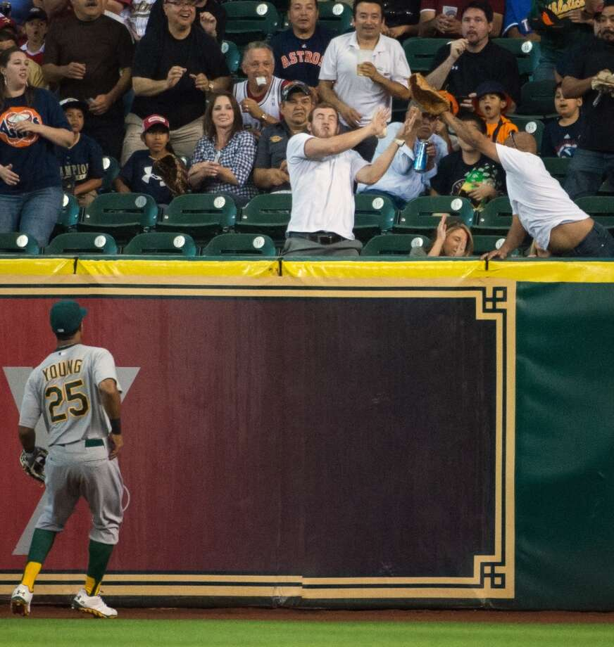 Athletics center fielder Chris Young watches as fans try to catch a home run by Astros catcher Jason Castro.