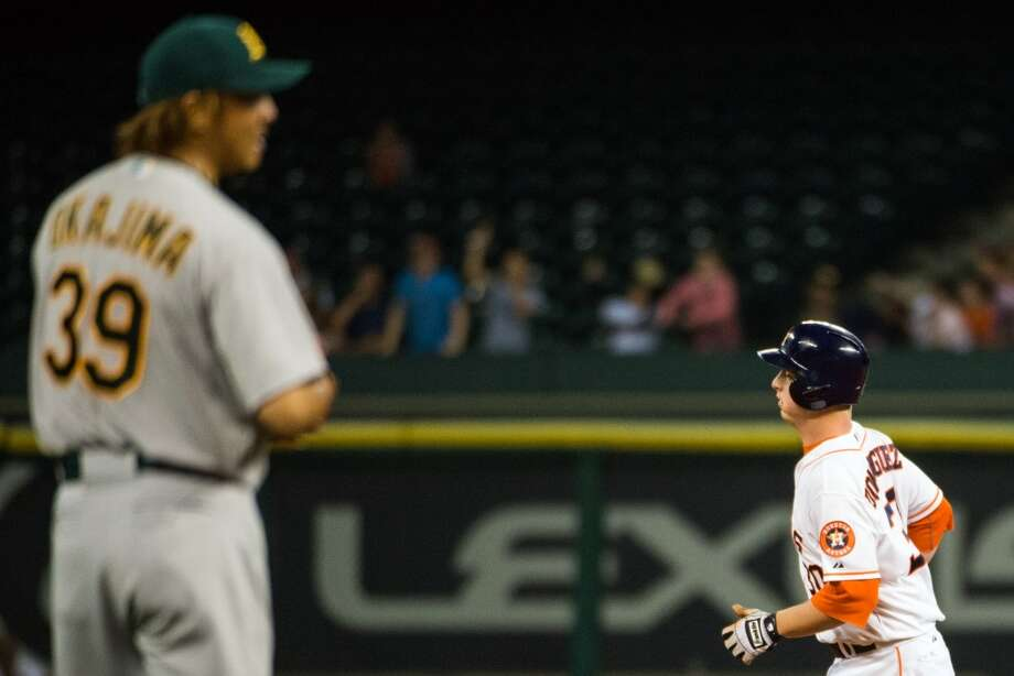 Astros third baseman Matt Dominguez, right, rounds the bases after hitting a home run off of Athletics relief pitcher Hideki Okajima, left, during the seventh inning.