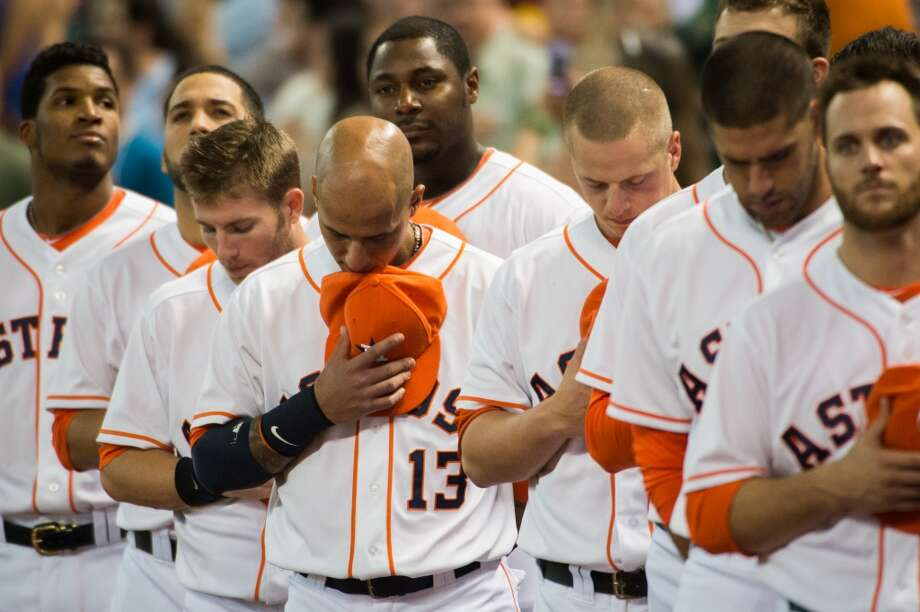 Astros shortstop Ronny Cedeno bows his head during the national anthem.