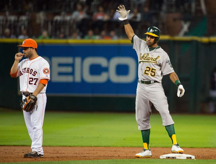 Astros second baseman Jose Altuve, left, looks away as Athletics outfielder Chris Young reaches second with a two-run double.