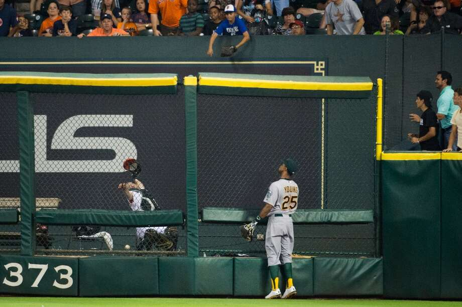 Athletics right fielder Chris Young (25) watches as Astros bullpen catcher Javier Bracamonte tries to make a catch on a home run by catcher Jason Castro.