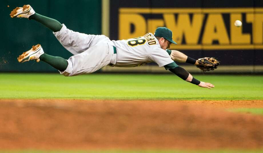 Athletics second baseman Eric Sogard dives for a single off the bat of Astros center fielder Robbie Grossman.