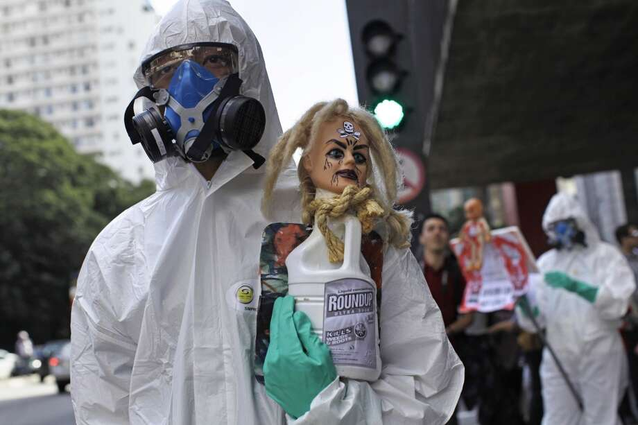 "A protester wearing a protective suit and mask holds up a bottle of Monsanto's Roundup herbicide during a protest against Monsanto in Sao Paulo, Brazil, Saturday, May 25, 2013. Marches and rallies against seed giant Monsanto were held across the U.S. and in dozens of other countries Saturday. ""March Against Monsanto"" protesters say they want to call attention to the dangers posed by genetically modified food and the food giants that produce it."