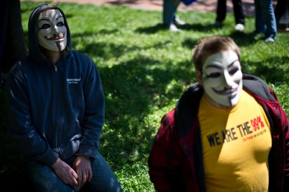 Activists wearing Anonymous masks listen to speakers during a demonstration against agribusiness giant Monsanto and genetically modified organisms (GMO) in front of the White House in Washington on May 25, 2013.