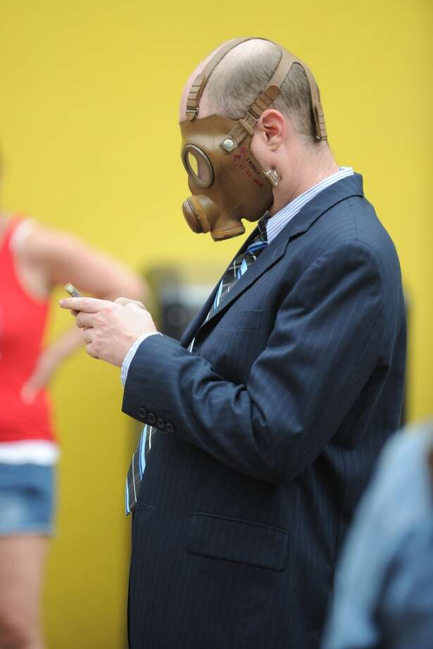 A protestor dressed in a gas mask and a suit checks his smart phone during a protest against chemical giant Monsanto in Los Angeles, California, May 25, 2013. Marches and rallies against Monsanto and genetically modified organisms (GMO) food and seeds were held across the U.S. and in other countries with protestors calling attention to the dangers posed by GMO food.