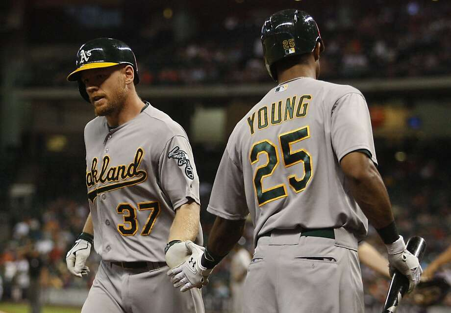Oakland Athletics' Brandon Moss (37) is congratulated by teammate Chris Young (25) after hitting a solo home run in the fourth inning during a baseball game against the Houston Astros, Saturday, May 25, 2013, in Houston. (AP Photo/Patric Schneider) Photo: Patric Schneider, Associated Press