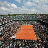Spectators at Philippe Chatrier court, or central court, watch an exhibition game between France's Richard Gasquet and Tomas Berdych of Czech Republic for the 2013 French Open tennis tournament, at Roland Garros stadium in Paris, Saturday May, 25, 2013. (AP Photo/Christophe Ena)