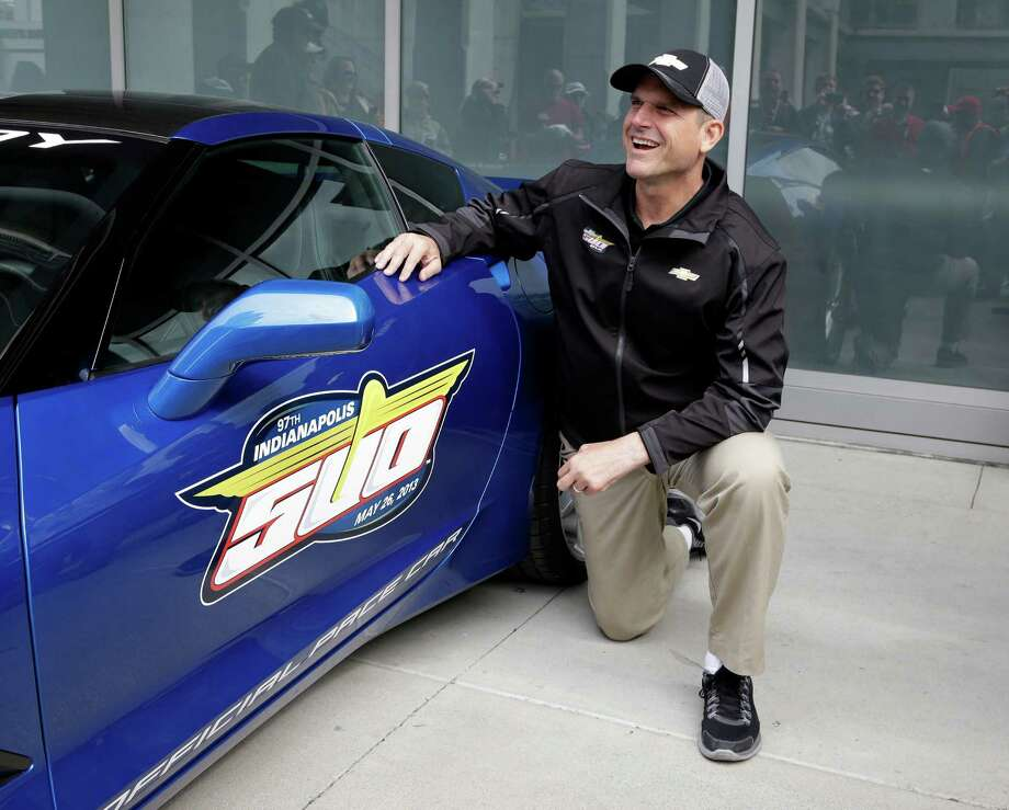 San Francisco 49ers head football coach Jim Harbaugh talks with fans as he poses for photos in Indianapolis, Saturday, May 25, 2013, next to the Chevrolet Corvette Stingray he will drive to lead the field for the start of the Indianapolis 500 auto race at the Indianapolis Motor Speedway on Sunday. (AP Photo/Michael Conroy) Photo: Michael Conroy