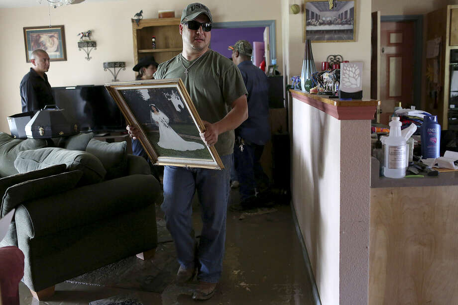Anthony Wilfong carries Celia Olivarez's wedding portrait out of her home, which was flooded with several feet of water on Espada Road. The wedding picture was taken at nearby Mission Espada and was undamaged by the flood. Photo: Photos By Lisa Krantz / San Antonio Express-News