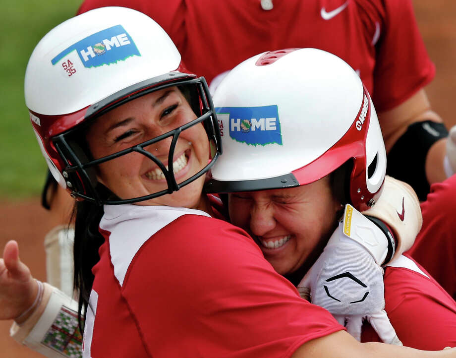 Oklahoma's Lauren Chamberlain, left, hugs Shelby Pendley after Pendley homered in the top-seeded Sooners' 8-0 victory over  Texas A&M at Norman, Okla., on Saturday that advanced OU to the Women's College World Series for the third consecutive year. Photo: STEVE SISNEY, MBI / THE OKLAHOMAN