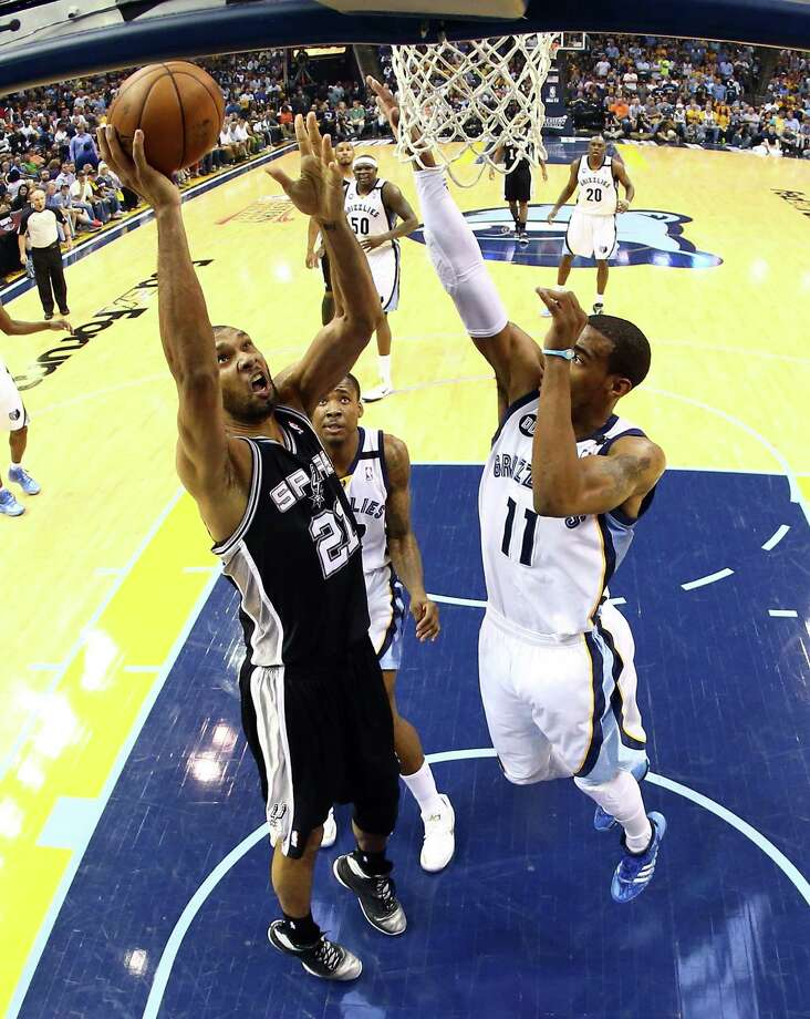 San Antonio's Tim Duncan scores over Memphis' Mike Conley (11) for two of his 24 points Saturday. Photo: Ronald Martinez, Staff / 2013 Getty Images
