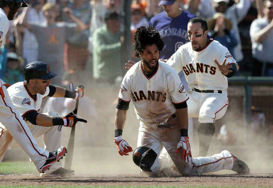 San Francisco's Angel Pagan, center, comes up celebrating with Marco Scutaro, left, and Andres Torres after his inside-the-park two-run homer in the 10th inning gave the Giants a 6-5 victory over visiting Colorado on Saturday. Photo: Jeff Chiu, STF / AP