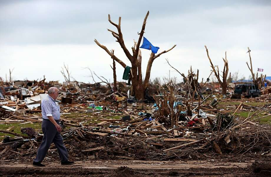MOORE, OK - MAY 25:  A man walks through a tornado ravaged neighborhood on May 25, 2013 in Moore, Oklahoma. The tornado of EF5 strength and two miles wide touched down May 20 killing at least 24 people and leaving behind extensive damage to homes and businesses. U.S. President Barack Obama promised federal aid to supplement state and local recovery efforts.  (Photo by Tom Pennington/Getty Images) Photo: Tom Pennington, Getty Images