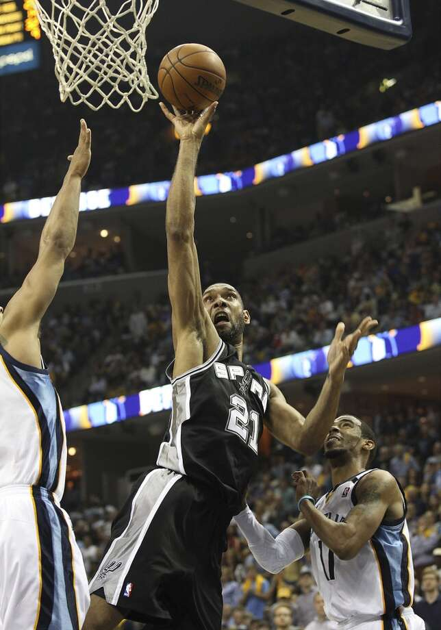 The Spurs' Tim Duncan (21) shoots over the Grizzlies' Jerryd Bayless (7) and Mike Conley (11) in Game 3 of the 2013 Western Conference Finals at the FedEx Forum in Memphis on Saturday, May 25, 2013. Spurs defeated the Grizzlies, 104-93, in overtime. (Kin Man Hui / San Antonio Express-News)