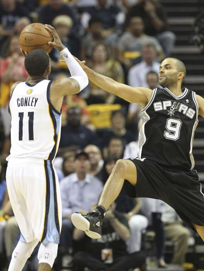 The Spurs' Tony Parker (9) reaches out to attempt a block against the  Grizzlies' Mike Conley (11) in Game 3 of the 2013 Western Conference Finals at the FedEx Forum in Memphis on Saturday, May 25, 2013. Spurs defeated the Grizzlies, 104-93, in overtime. (Kin Man Hui / San Antonio Express-News)
