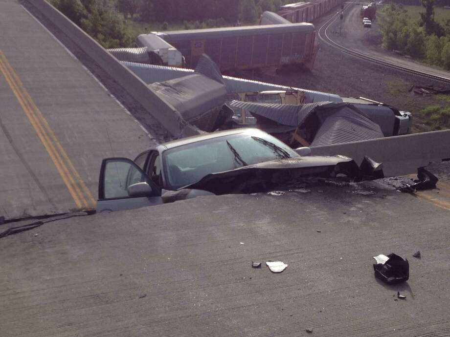 A car lies in-between damaged sections of a highway overpass near Rockview, Mo. on Saturday, May 25, 2013. Authorities said the roadway collapsed when rail cars slammed into one of the bridge's pillars after a cargo train collision. Seven people were injured, though none seriously. Photo: AP