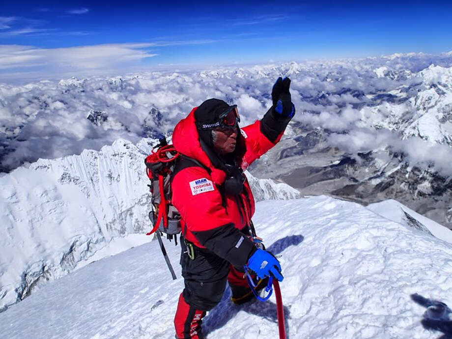 In this photo distributed by MIURA DOLPHINS Co., Ltd, 80-year-old Japanese extreme skier Yuichiro Miura stands atop the summit of Mount Everest as he becomes the oldest person to climb the world's tallest mountain Thursday, May 23, 2013. Miura, who also conquered the 29,035-foot (8,850-meter) peak when he was 70 and 75, reached the summit at 9:05 a.m. local time, according to a Nepalese mountaineering official and Miura's Tokyo-based support team. (AP Photo/MIURA DOLPHINS Co., Ltd) Photo: AP