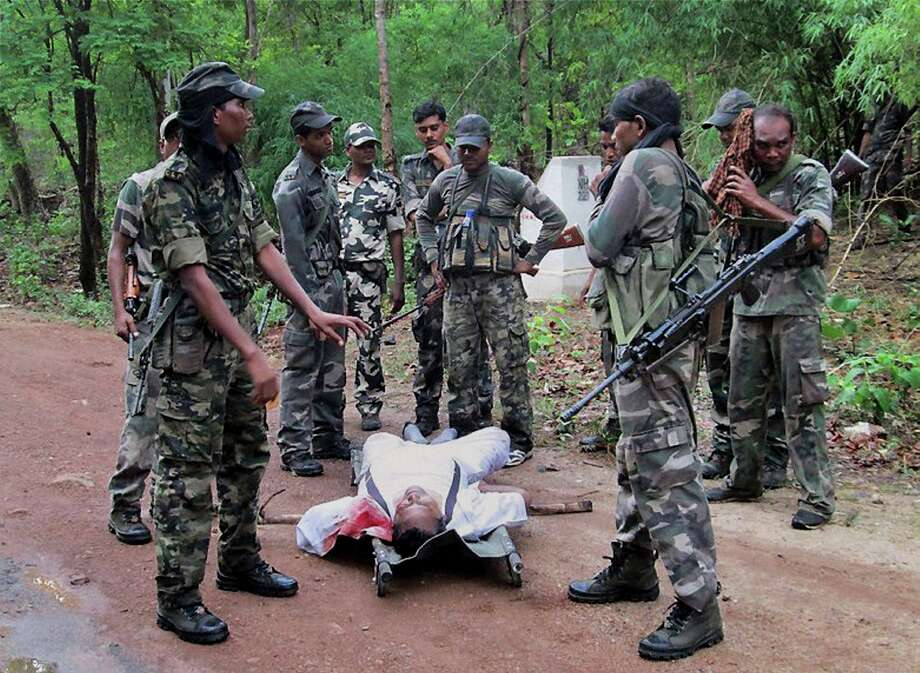 Indian security personnel stand near the body of one of the victims of Saturday's Maoist attack in a densely forested area in Bastar, about 345 kilometers (215 miles) south of Raipur, Chhattisgarh state, India, Sunday, May 26, 2013. Officials reacted with outrage Sunday to an audacious attack by about 200 suspected Maoist rebels who set off a roadside bomb and opened fire on a convoy carrying Indian ruling Congress party leaders and members in an eastern state, killing at least 24 people and wounding 37 others. Photo: AP