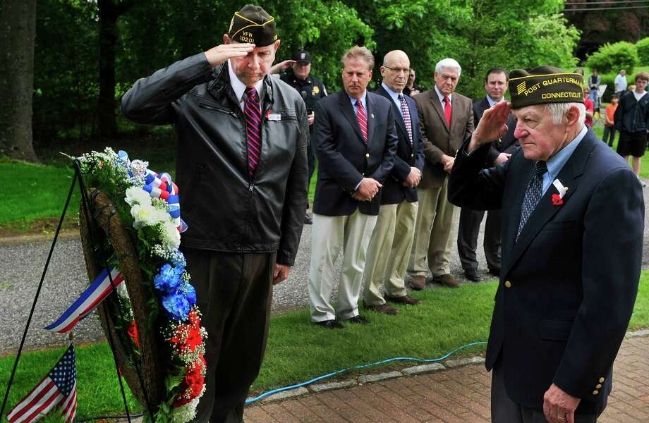 Gene Roberts, left, and Fred Busch, both members of VFW Post 10201, salute, after placing a wreath to honor Brookfield's fallen heros, during a memorial ceremony in Williams Park as part of the Memorial Day parade in Brookfield, Conn. Sunday, May 26, 2013. Photo: Michael Duffy / The News-Times
