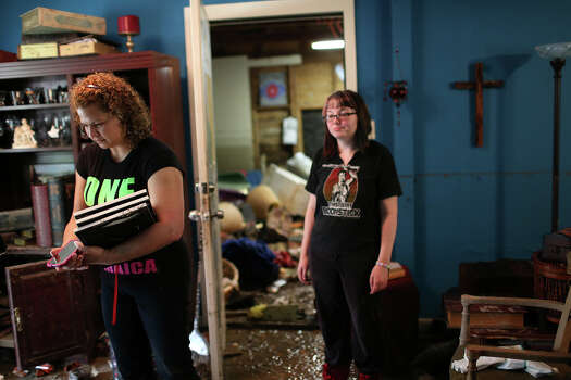 Crystal Valentin, 32, left, and her sister, Rhoda Council, 23, check out the flood damage at their parent's house on Mission Road, Sunday, May 26, 2013. According to residents of the area, the neighborhood flooded after record setting rainfall on the city's north side lead to the opening of the flood gates at Olmos Basin Dam Saturday. Photo: Jerry Lara, San Antonio Express-News / San Antonio Express-News
