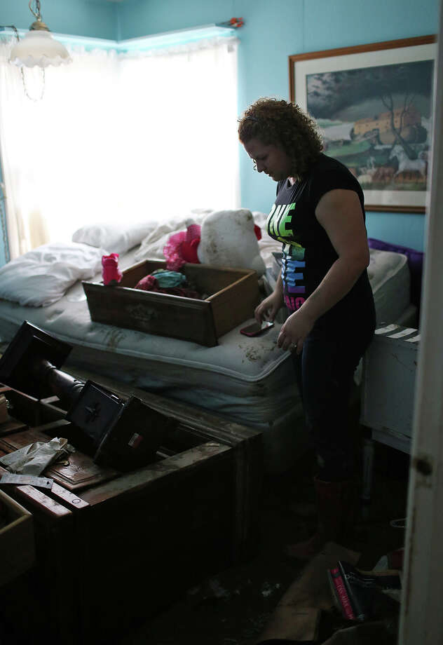 Crystal Valentin, 32, checks out flood damage at her parent's home on Mission Road, Sunday, May 26, 2013. According to residents of the area, the neighborhood flooded after record setting rainfall on the city's north side lead to the opening of the flood gates at Olmos Basin Dam Saturday. Photo: Jerry Lara, San Antonio Express-News / San Antonio Express-News