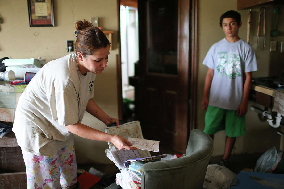 Sara Perez, 29, check out a wedding album at her flood damaged house on Mission Road, Sunday, May 26, 2013. According to residents of the area, the neighborhood flooded after record setting rainfall on the city's north side lead to the opening of the flood gates at Olmos Basin Dam Saturday. With Perez is her son, Eddie, 12. Photo: Jerry Lara, San Antonio Express-News / San Antonio Express-News