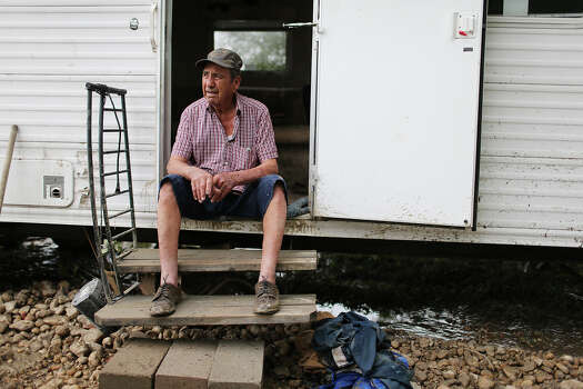Ermilo Garza, 80, sits by his trailer on land off Mission Road, Sunday, May 26, 2013. According to residents of the area, the neighborhood flooded after record setting rainfall on the city's north side lead to the opening of the flood gates at Olmos Basin Dam Saturday. Garza refused to evacuate and rode out the flooding inside his trailer. Photo: Jerry Lara, San Antonio Express-News / San Antonio Express-News