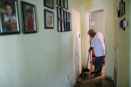 Robert Sanchez, 57, helsp clean up his son's house on Mission Road, Sunday, May 26, 2013. According to residents of the area, the neighborhood flooded after record setting rainfall on the city's north side lead to the opening of the flood gates at Olmos Basin Dam Saturday. Photo: Jerry Lara, San Antonio Express-News / San Antonio Express-News