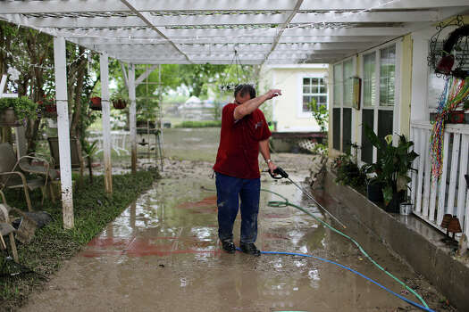 Norman Garza, 63, wipes his brow while cleaning up at his home on Mission Road, Sunday, May 26, 2013. According to residents of the area, the neighborhood flooded after record setting rainfall on the city's north side lead to the opening of the flood gates at Olmos Basin Dam Saturday. Photo: Express-News File Photo, San Antonio Express-News / © 2013 San Antonio Express-News