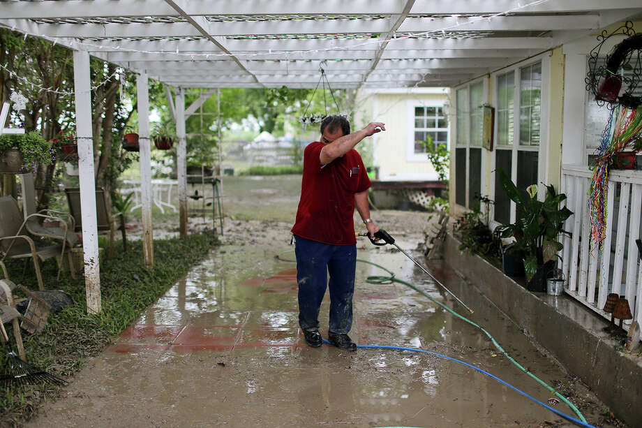 Norman Garza, 63, wipes his brow while cleaning up at his home on Mission Road after a record setting rainfall in late May. About 18,165 structures in Bexar COunty are in the flood plain.  Photo: Express-News File Photo, San Antonio Express-News / © 2013 San Antonio Express-News