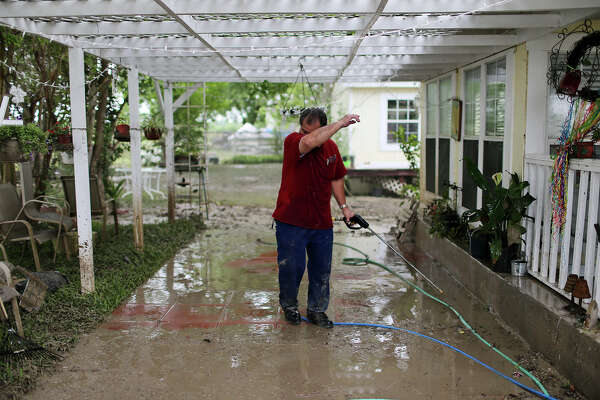 Norman Garza, 63, wipes his brow while cleaning up at his home on Mission Road, Sunday, May 26, 2013. According to residents of the area, the neighborhood flooded after record setting rainfall on the city's north side lead to the opening of the flood gates at Olmos Basin Dam Saturday.