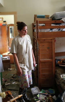 Sara Perez, 29, looks around her sons' room at their home on Mission Road, Sunday, May 26, 2013. According to residents of the area, the neighborhood flooded after record setting rainfall on the city's north side lead to the opening of the flood gates at Olmos Basin Dam Saturday. Photo: Jerry Lara, San Antonio Express-News / San Antonio Express-News