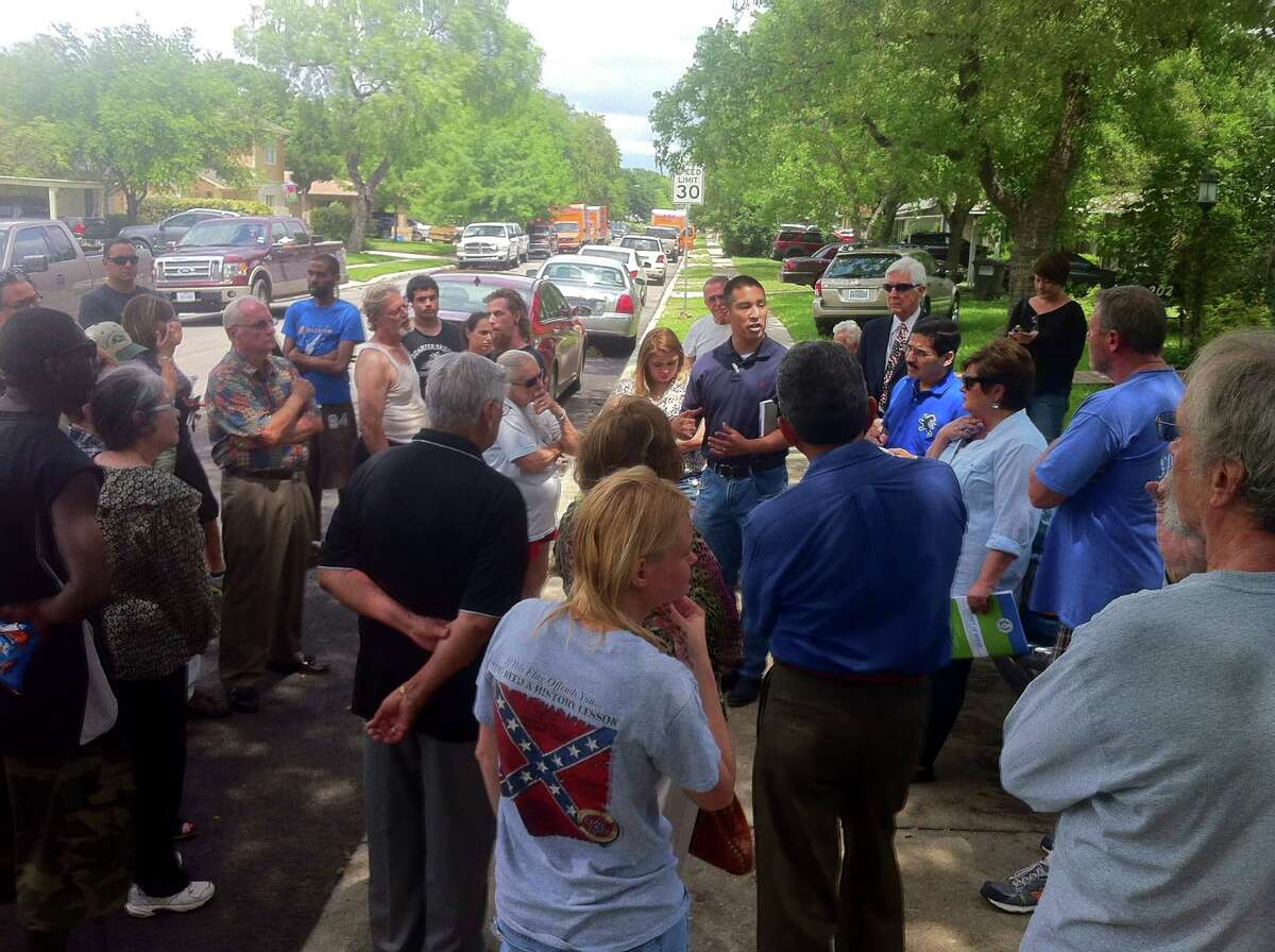 Bexar County executive staff member Thomas Guevara (center) speaks to residents of the flooded 200 block of Barbara Drive near McCullough Avenue about a lack of flood control.