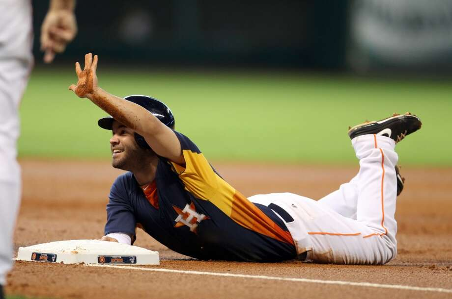 Jose Altuve of the Astros reacts after sliding into third base.