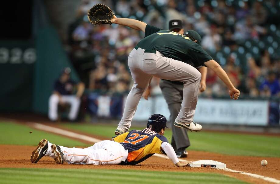 Nate Frieman of the A's jumps over Astros second baseman Jose Altuve.