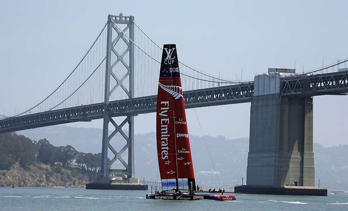 Emirates Team New Zealand sails past the San Francisco-Oakland Bay Bridge back to its waterfront base after a training run for the America's Cup, Thursday, May 23, 2013, in San Francisco. Body armor and high-visibility helmets for crew members are among the recommendations made by a group of sailing experts addressing safety concerns in the America's Cup. The group led by regatta director Iain Murray unveiled 37 proposals on Wednesday, two weeks after a member of the Artemis Racing crew died when the catamaran capsized during a training run on San Francisco Bay. (AP Photo/Eric Risberg)