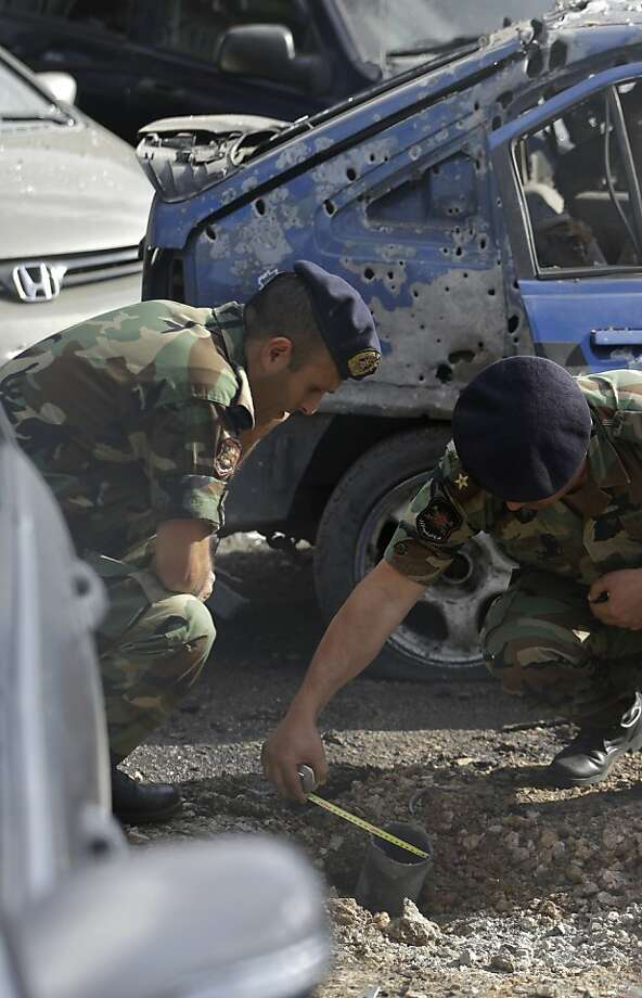 Lebanese army officers investigate a rocket hit, one of two in Beirut neighborhoods that are strongholds of Hezbollah. Photo: Hussein Malla, Associated Press