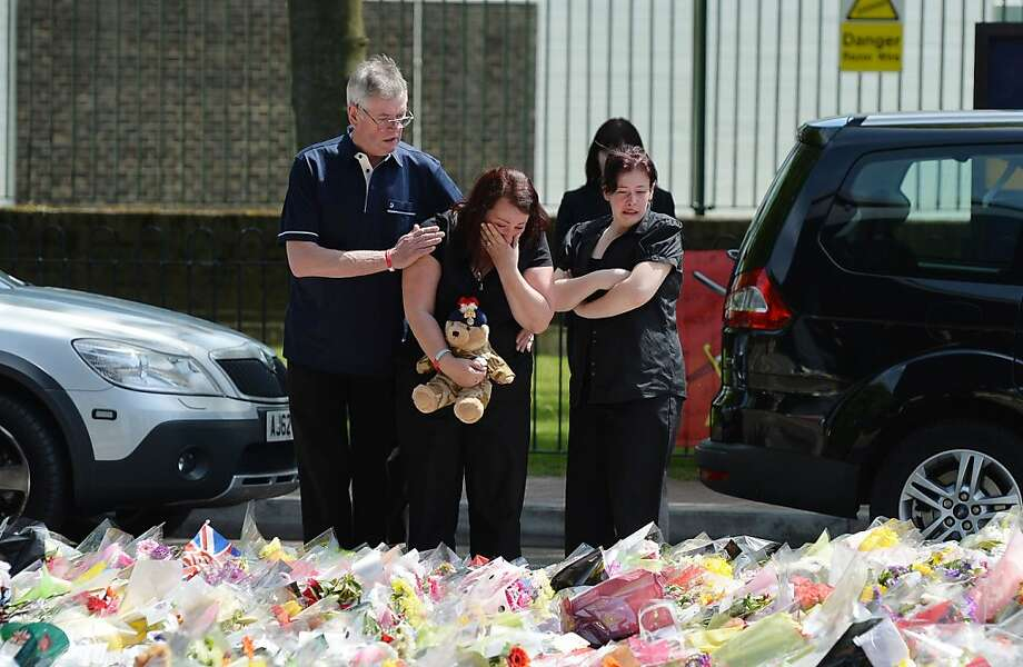 Lyn Rigby, mother of Drummer Lee Rigby, holding a teddy bear joins other family members as they look at floral tributes outside Woolwich Barracks left by well wishers as they visited the scene of the 25-year-old soldier's murder in Woolwich, south-east London, Sunday May 26, 2013. (AP Photo/John Stillwell, PA). UNITED KINGDOM OUT - NO SALES - NO ARCHIVES Photo: John Stillwell, Associated Press