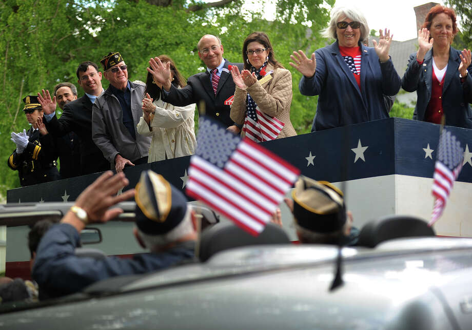 Dignitaries wave from the reviewing stand to a car load of veterans at the annual Memorial Day Parade in Milford, Conn. on Sunday, May 26, 2013. Photo: Brian A. Pounds