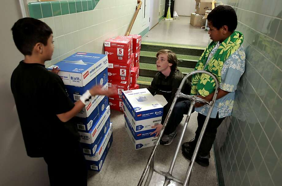 Nicholas Persky (center) with the help of students Alfredo Leverman (left) and David Funaki delivers  130 reams of paper to Bret Harte Middle School in S.F. He got the paper mostly for free with coupons. Photo: Michael Macor, The Chronicle