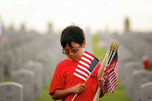 Volunteer 10-year-old Brandon Miller, of Boy Scout troop 414 holds a handful of flags at a grave site, during an event lead by Flags for Fallen Vets, Sunday, May 26, 2013 at the Houston National Cemetery in Houston, Texas. The group has organized a team of volunteers to place a single american flag at each grave site honoring the soldiers and their service. Photo: © TODD SPOTH, 2013 / © TODD SPOTH, 2013