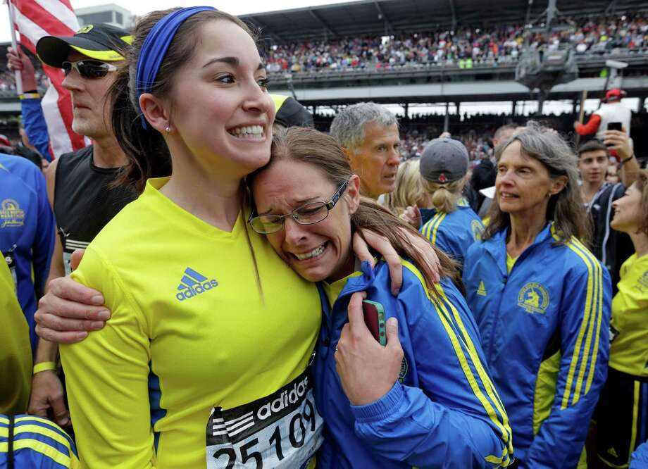 Rachel Bolka, left, of Indianapolis, and Kelli Wheeler, two of the approximately 35 runners from the 2013 Boston Marathon unable to finish the race due to the tragic bombings, hug after they complete the distance by crossing finish line at the Indianapolis Motor Speedway  before the start of the 97th Indianapolis 500 auto race. (AP Photo/Darron Cummings) Photo: Darron Cummings, Associated Press / AP