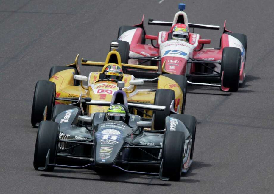 Tony Kanaan, of Brazil, (11) takes the lead from Ryan Hunter-Reay(1) on the 197th lap on his way winning the Indianapolis 500 auto race at the Indianapolis Motor Speedway in Indianapolis, Sunday, May 26, 2013. Justin Wilson (19), of England, finished fifth. (AP Photo/AJ Mast) Photo: AJ Mast, Associated Press / FR123854 AP