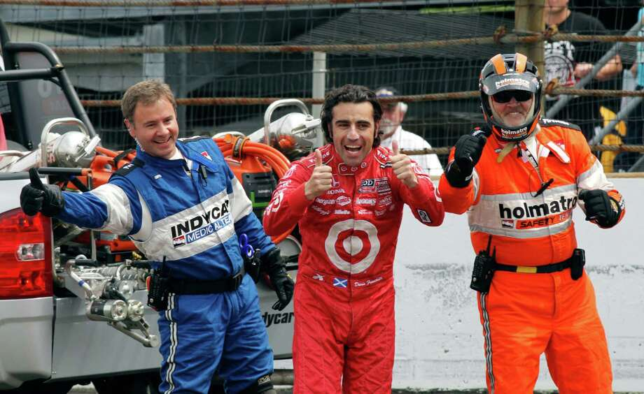 Dario Franchitti, center, of Scotland, along with safety team members, left and right, congratulate Tony Kanaan, of Brazil, who drives by under caution on his way winning the Indianapolis 500 auto race at Indianapolis Motor Speedway in Indianapolis, Sunday, May 26, 2013. (AP Photo/Tom Hemmer) Photo: Tom Hemmer, Associated Press / AP