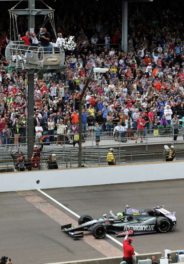 Tony Kanaan, of Brazil, celebrates as he crosses the finish line to win the Indianapolis 500 auto race at Indianapolis Motor Speedway in Indianapolis, Sunday, May 26, 2013. (AP Photo/Dave Parker) Photo: Dave Parker, Associated Press / A{
