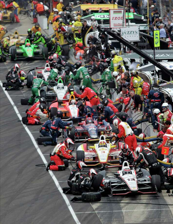 Teams, including those of Australia's Will Power (12) and Brazil's Helio Castroneves (3), pit during a yellow flag on lap 58 of the Indianapolis 500 auto race at Indianapolis Motor Speedway in Indianapolis, Sunday, May 26, 2013. (AP Photo/AJ Mast) Photo: AJ Mast, Associated Press / FR123854 AP